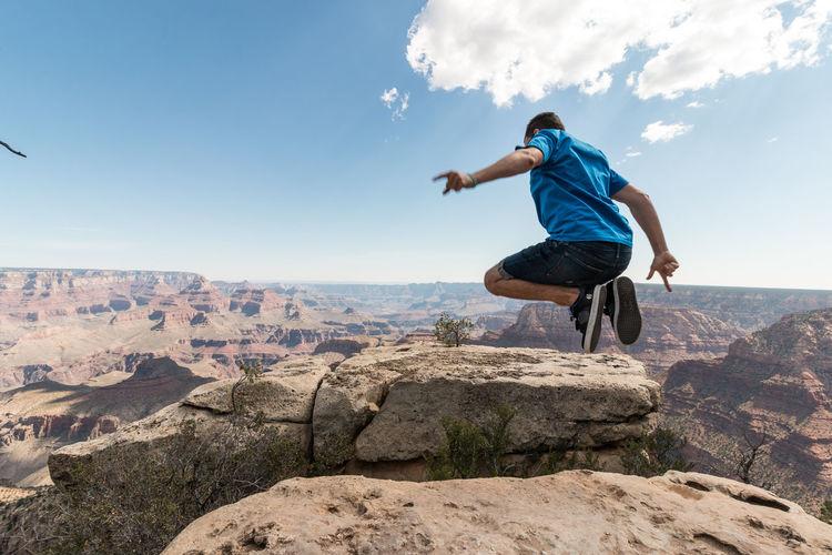 Full length of man jumping over cliff against sky