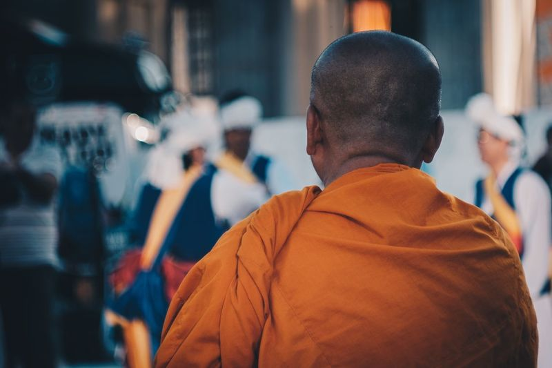 Rear View Of Monk Wearing Orange Traditional Cloth In City