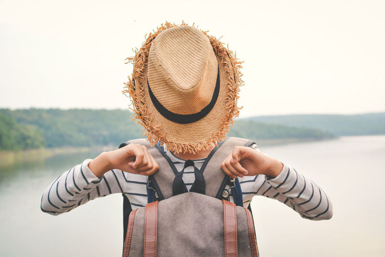 Close-Up Of Boy Wearing Hat Against Sea Against Clear Sky