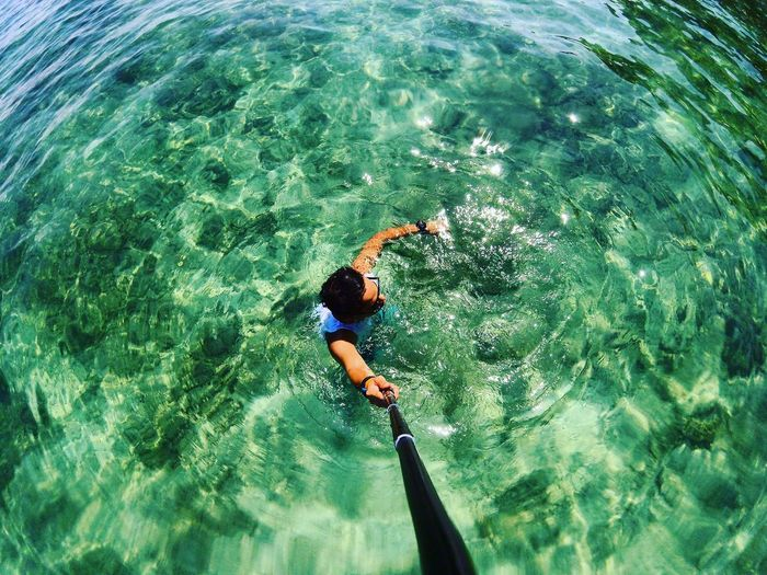 High angle view of man holding monopod while swimming in sea