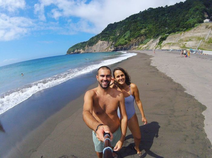 Portrait of happy couple taking selfie at beach on sunny day