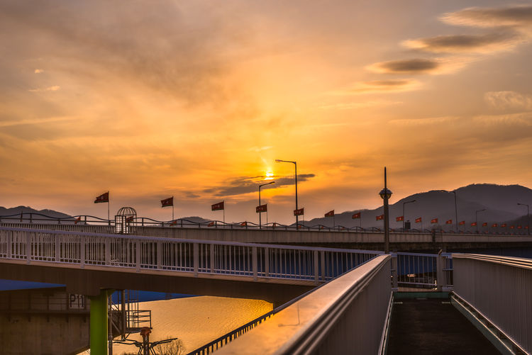 LINE Lines Riverside Architecture Bridge - Man Made Structure Building Exterior City Cloud - Sky Day Flags Illuminated Nature No People Orange Color Outdoors River Road Sky Sunset Water