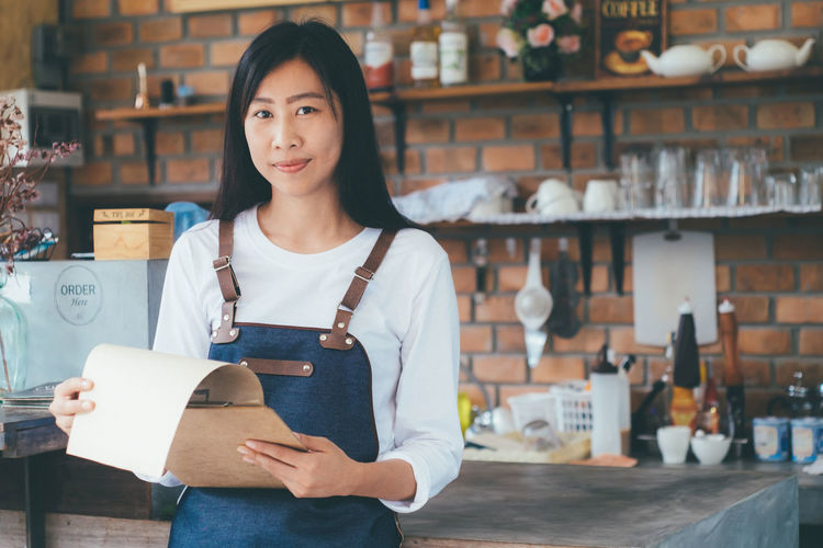 Portrait Of Owner With Clipboard Standing In Store