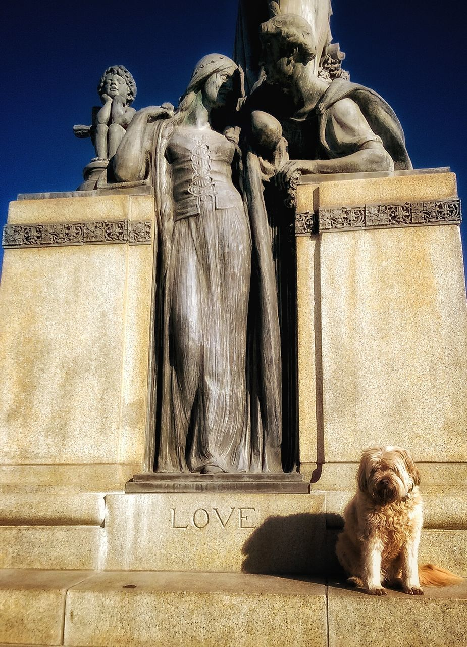 statue, sculpture, dog, human representation, male likeness, art and craft, pets, no people, outdoors, built structure, domestic animals, day, sunlight, architecture, mammal, building exterior