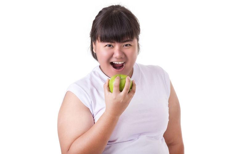 Portrait of smiling man holding apple against white background