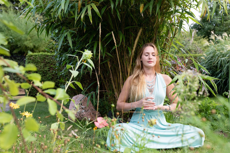 Young woman holding wineglass while sitting against plants