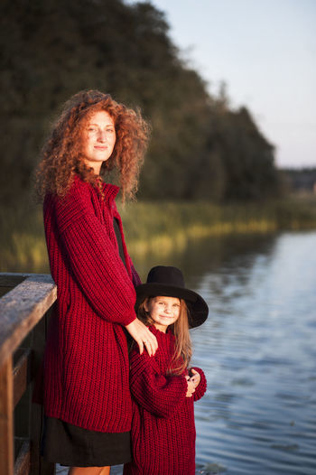 Adult Beautiful Woman Beauty Curly Hair Day Happiness Hat Lake Leisure Activity Lifestyles Long Hair Looking At Camera Outdoors Portrait Real People Red Redhead Smiling Standing Togetherness Two People Water Women Young Adult Young Women