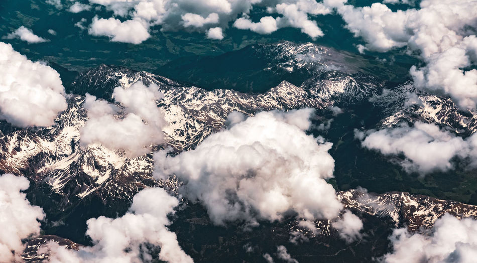 Aerial view of cloudscape over snowcapped mountains
