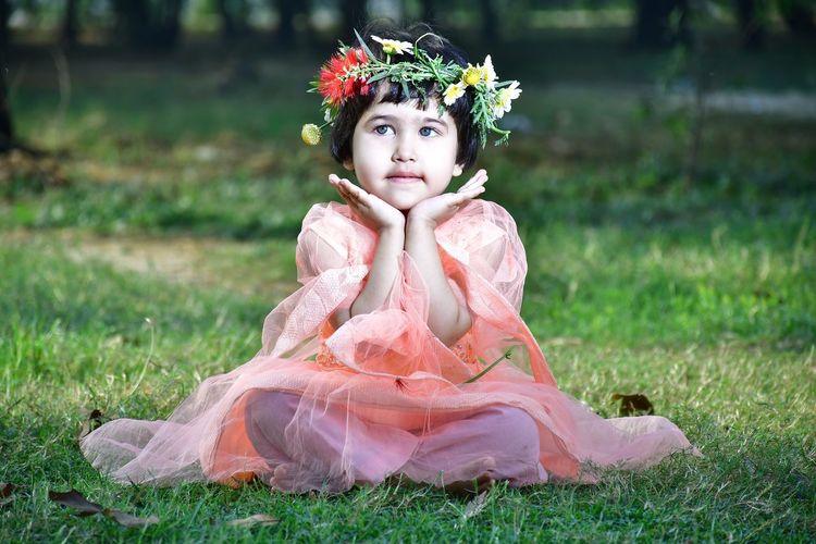 Happy girl sitting on field for festival