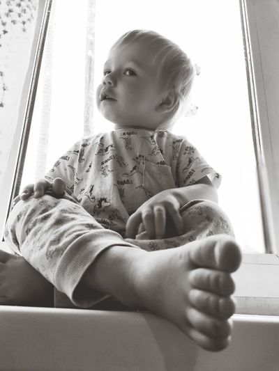 Cute baby girl sitting on window at home