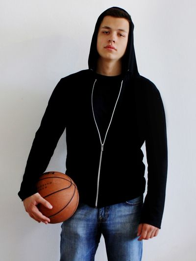 Portrait Of Man With Basketball Standing Against Wall
