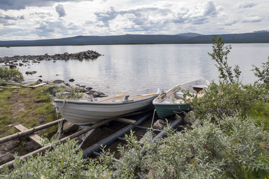 Beauty In Nature Boat Calm Day Hiking Trail Kungsleden Lakeshore Mountain Mountain Range Nature Nautical Vessel Nordic Light Outdoors Remote Row Boat Rowing Boat Sarek Shoreline Tranquility Water