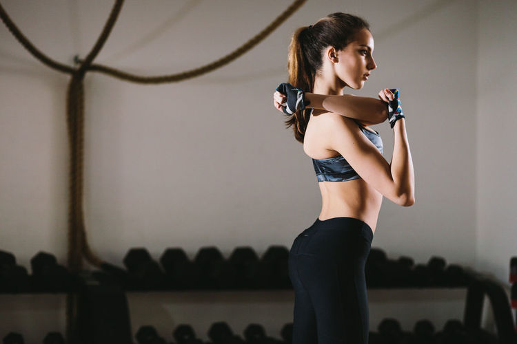 Side View Of Young Woman Exercising While Standing Against Wall In Gym