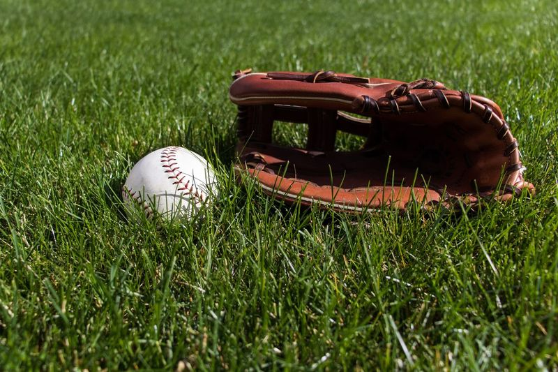 Close-up of baseball glove and ball on grass