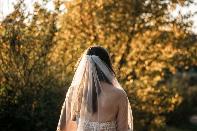 Rear view of bride standing against trees