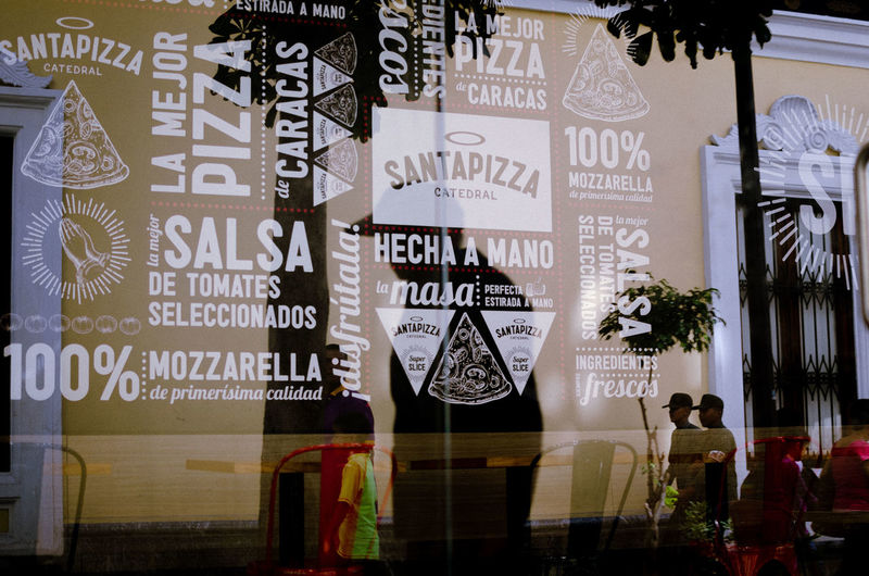 Santa Pizza Text Communication Western Script Architecture Glass - Material Script Non-western Script Information Window Built Structure Group Of People Advertisement Sign City Transparent Building Exterior Day Store Outdoors Information Sign Message Menu EyeEm Best Shots EyeEm Selects