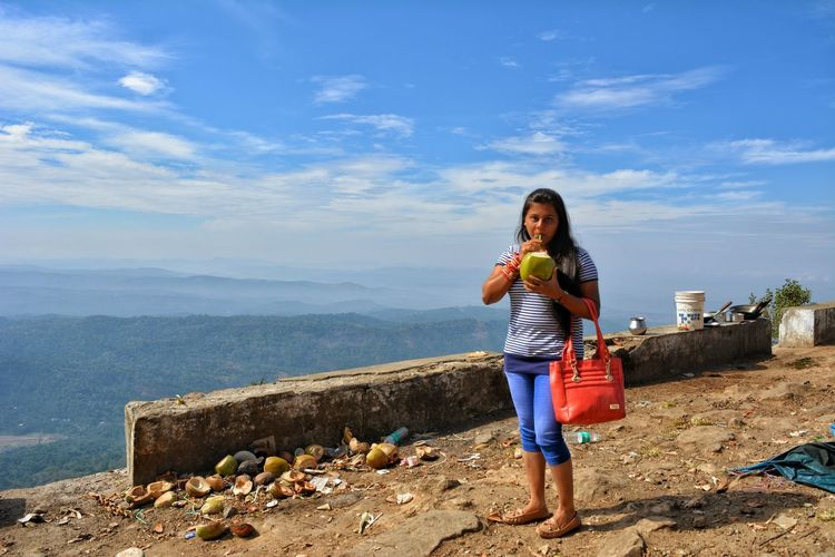 Portrait of young woman drinking coconut water while standing on mountain against sky