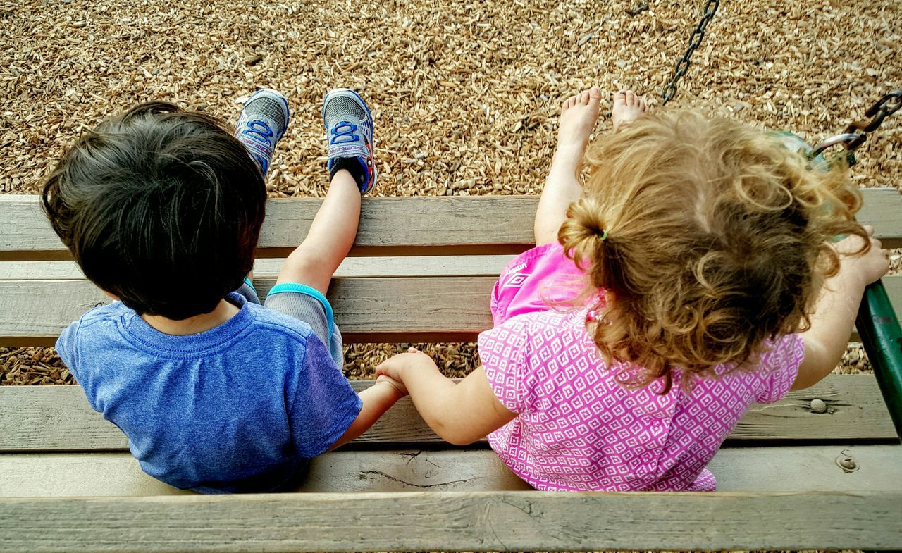 High angle view of siblings holding hands while sitting on bench