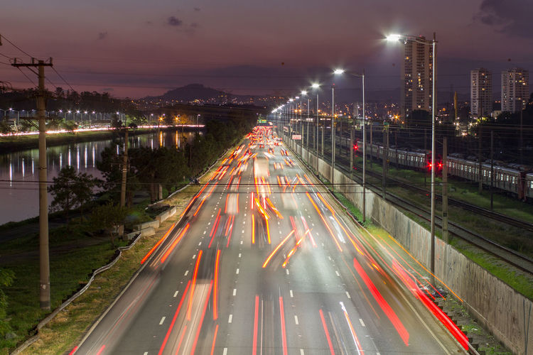 Beggining the night, bright lights and vehicles in transit. sao paulo city highway beside the river.
