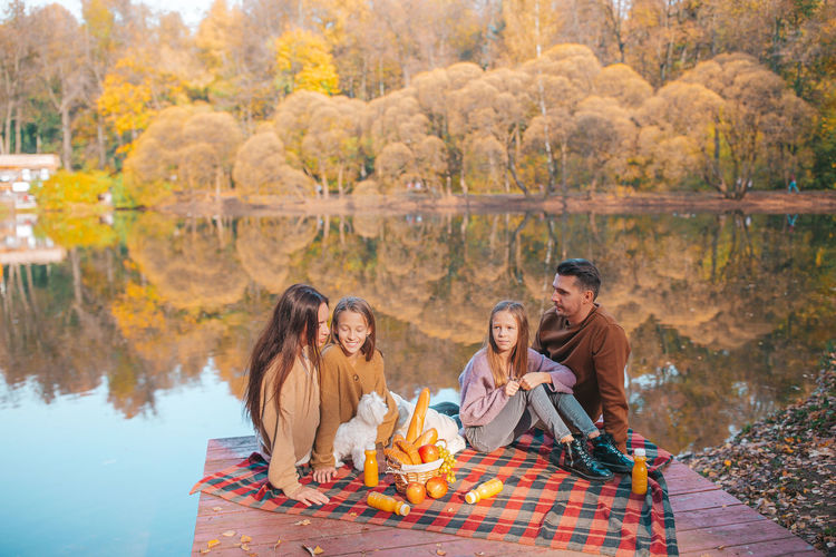 Group of people sitting on autumn leaves