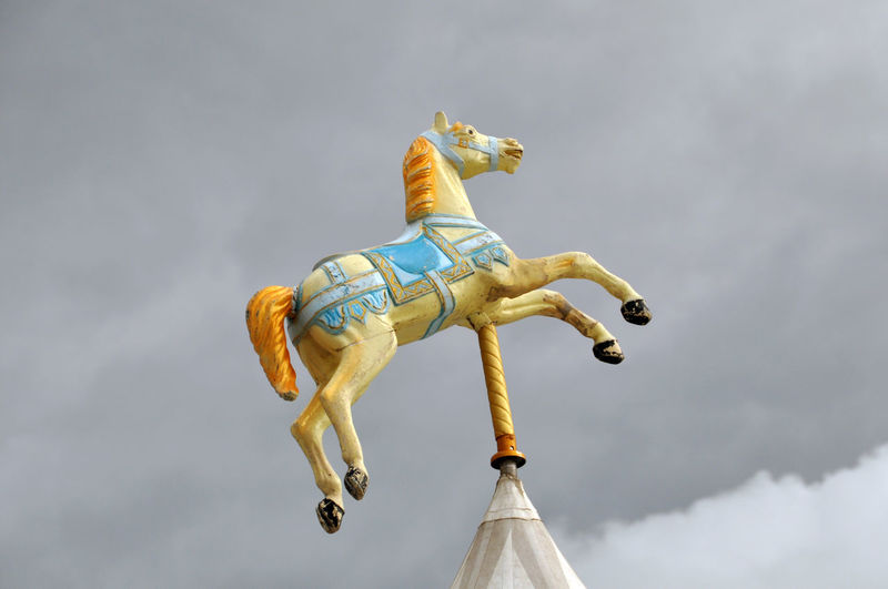 Low angle view of horse representation against sky