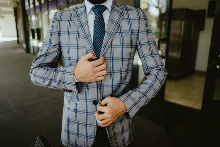 Midsection of businessman in checked pattern suit
