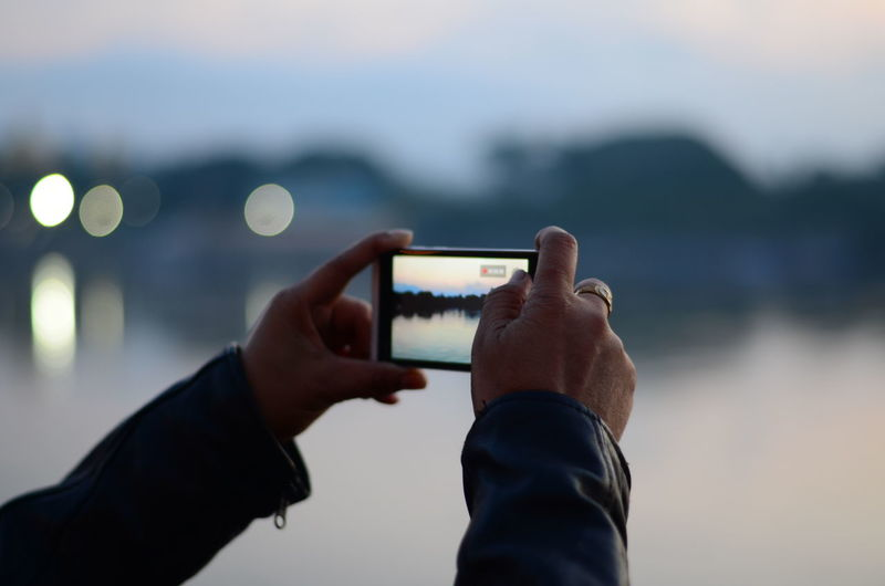 Midsection of man using mobile phone against sea