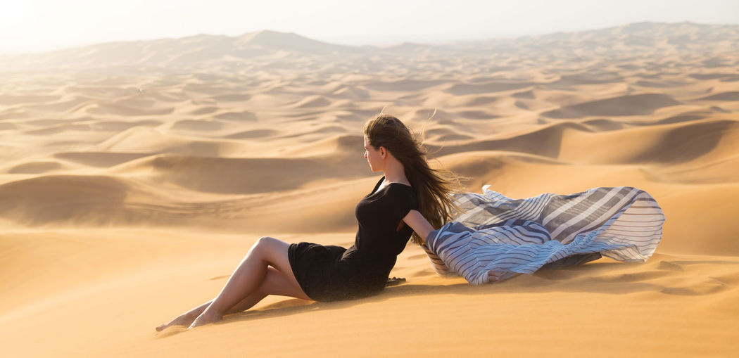 Side view of woman lying on sand