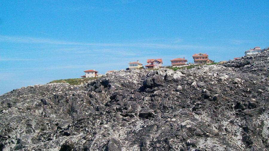 Houses on rocky mountain against sky