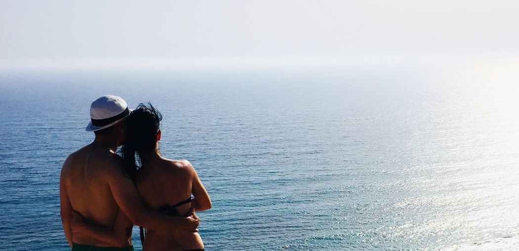 Water Sea Real People Men Leisure Activity Lifestyles Beauty In Nature Nature Standing People Shirtless Day Sky Waist Up Outdoors Rear View Horizon Over Water