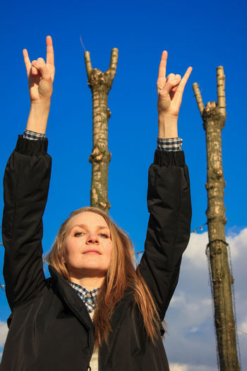 Portrait of woman showing rock sign with arms raised against blue sky