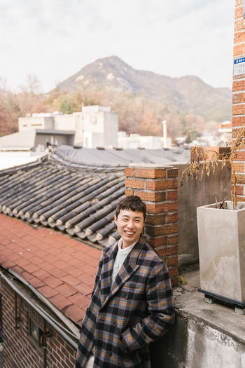 Portrait of smiling woman on roof against building