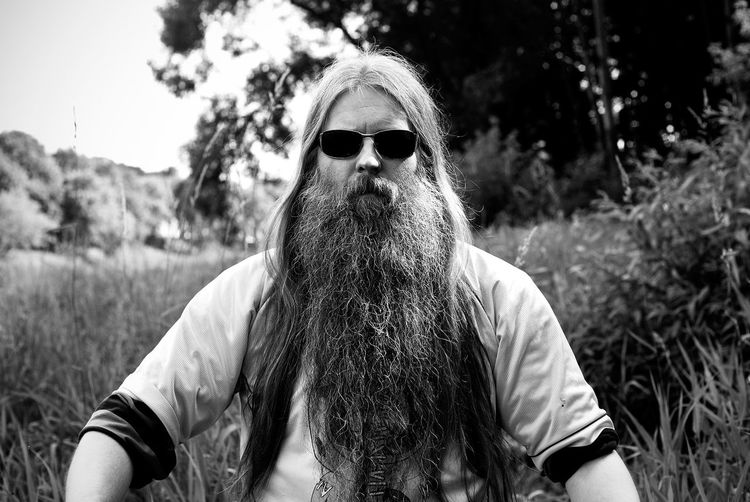 Portrait of bearded man wearing sunglasses against trees
