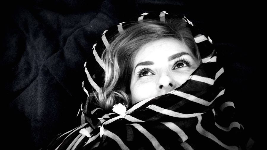 Thoughtful Woman Wrapped In Scarf Lying On Bed