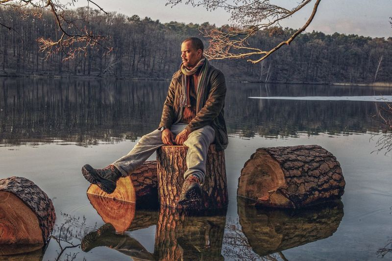 Full length of man looking at view while sitting on log in lake