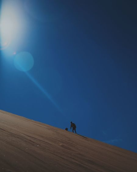 Man standing on mountain against clear blue sky