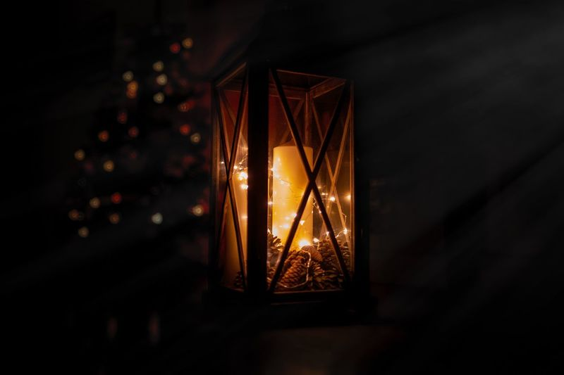 Close-up of illuminated candle in lantern at night