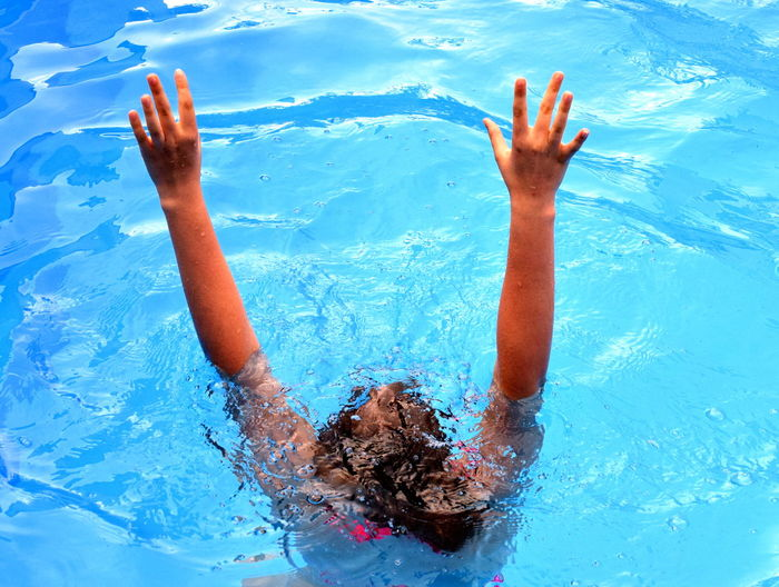 Woman With Arms Raised Drowning In Swimming Pool