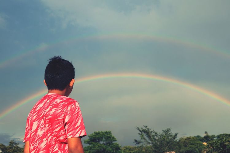 Side view of man looking at rainbow in sky