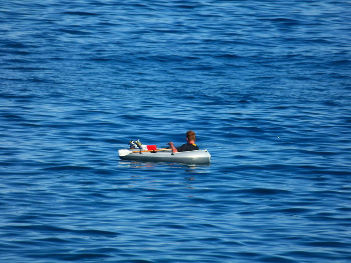 Rear view of man boating in sea