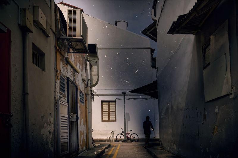 Man walking on alley amidst buildings in city