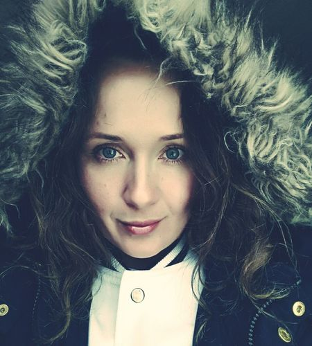 Close-up portrait of young woman in warm clothing against black background