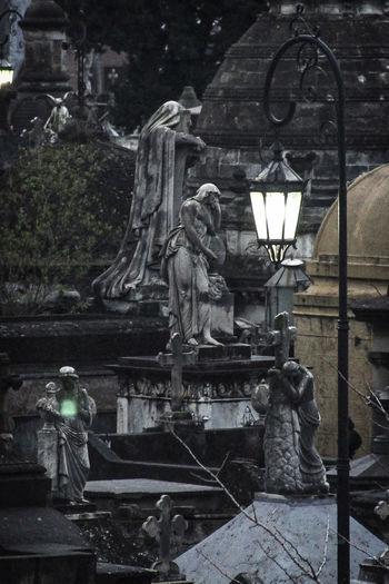 Statue against illuminated building