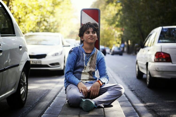 Full Length Of Homeless Boy Looking Away While Sitting Amidst Street