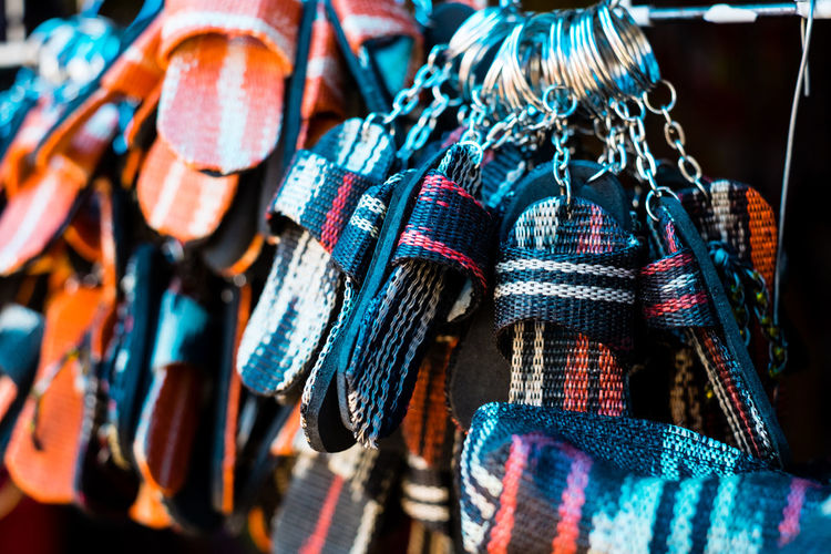 Close-Up Of Multi Slippers Shaped Key Rings Hanging For Sale At Street Market