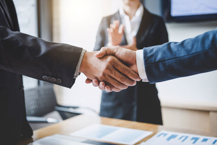 Cropped image of business people shaking hands over table