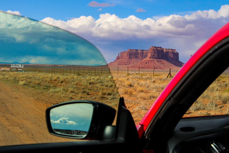 Car Land Vehicle Motor Vehicle Transportation Sky Glass - Material Cloud - Sky Mode Of Transportation Reflection Side-view Mirror Vehicle Interior Car Interior Nature Landscape Travel Transparent Beauty In Nature Day Road Mountain Outdoors No People Road Trip Vehicle Mirror Arizona Desert Monument Valley Arizona Sky