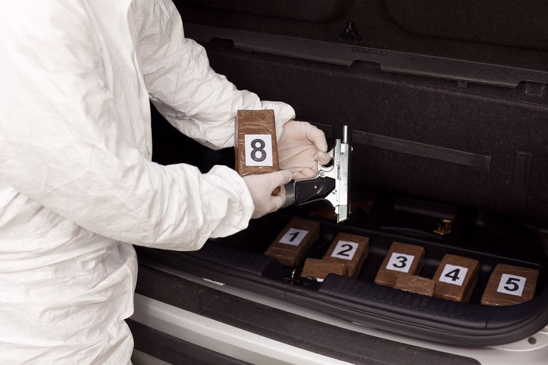 Midsection of person holding drug and gun by car trunk