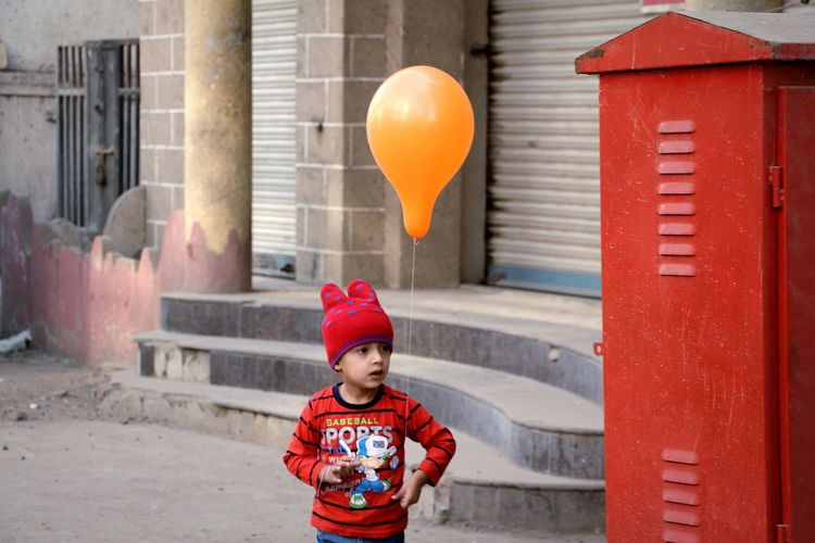 Portrait of cute boy with red balloons