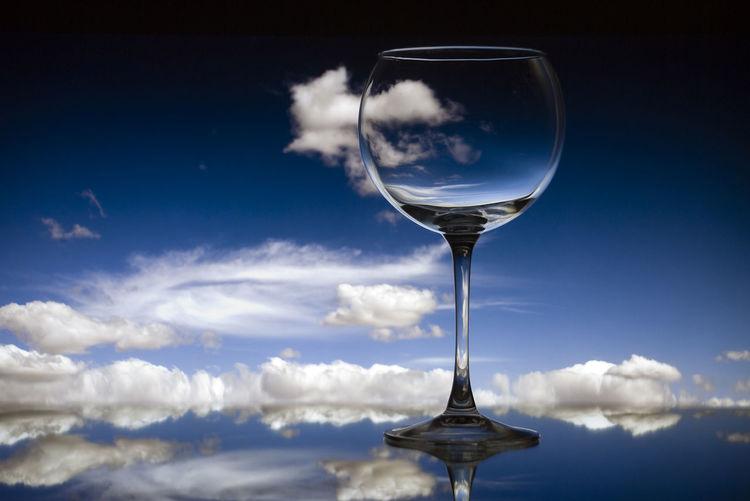 Digital composite image of beer glass against blue sky